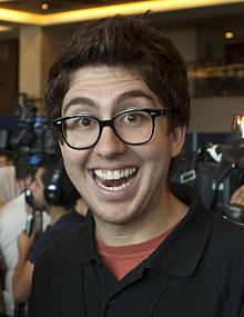 Amir Blumenfeld smiling widely, in front of a crowd of journalists with cameras, wearing a black polo shirt and horn-rimmed glasses