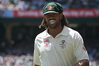 An unshaven man with dreadlocks and white sun lotion on his lips, wearing a baggy green cap and white cricket t-shirt.