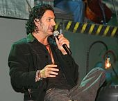 A man sitting with black shirt, black jacket, gray pants, with the left leg crossed over the right, holding a microphone in his left hand.