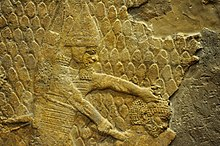 Relief depicting an Assyrian soldier about to behead a man