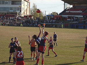 Victorian Women's Football League - The rucks reach for the ball after the umpire (in orange) has balled it up. Taken at the 2005 VWFL Division 1 Grand Final - Melbourne University MUGARS (black and blue) def. Darebin Falcons.