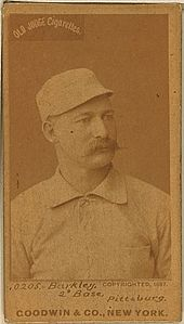 A baseball player is shown sitting, facing slightly right of the camera.