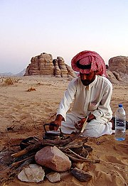 A young Bedouin lighting a camp fire in Wadi Rum, Jordan