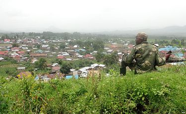 An M23 rebel sits on a hill above Bunagana