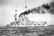 A large battleship cruises slowly near the coast. Wind blows the smoke emitted from the three funnels over the ship