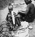 COLLECTIE TROPENMUSEUM Een Samo kind speelt met een speelgoedvliegtuig terwijl het haar van zijn moeder wordt gekapt TMnr 20010290.jpg