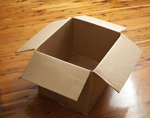 An open cardboard box on a wooden floor