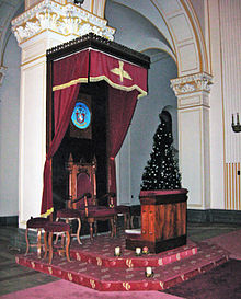 A polished wooden chair on a raised dais, under a polished wooden canopy trimmed with crimson curtains