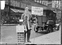 a man dressed as santa claus fundraising for volunteers of america on the sidewalk of street in chicago illinois in 1902 he is wearing a mask with a