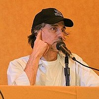 Upper body shot of man sitting behind desk with baseball cap speaking into a microphone
