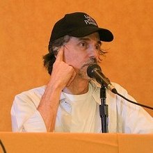 upper body shot of man sitting at desk with white shirt and black baseball cap speaking into microphone