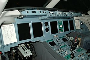 View of cockpit of modern jet airliner, showing a large array of displays and instruments.