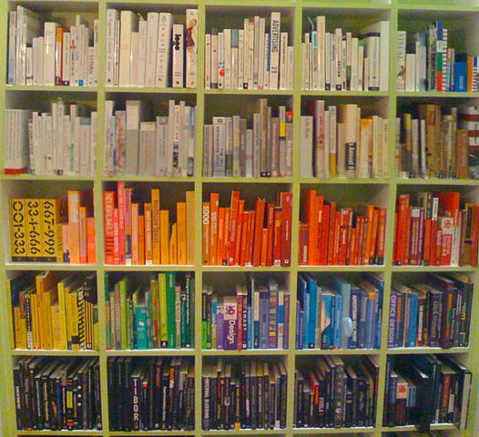 A bookcase where all the books have been organized according to the color of their spine: white on the top rows, then a row of orange and red, then yellow-green-blue in a gradient, then black on the bottom row.
