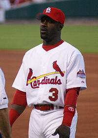 "A man in a white baseball uniform with ""Cardinals"" and ""3"" on the chest wearing red cap and armbands."