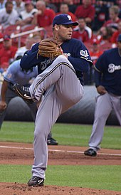 "A man, wearing a dark blue baseball cap with ""M"" in the centre, a dark blue baseball jersey with ""M"" on the left shoulder and the words ""BREWERS"" across the chest and black Nike cleats, does a leg kick as part of pitching a baseball."