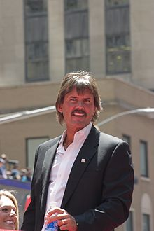 Dennis Eckersley in a black suit with the top of a water bottle in his right hand