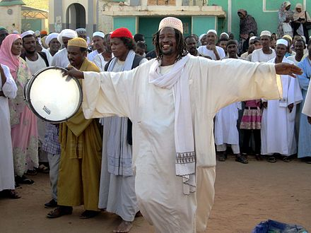 A Sufi dervish drums up the Friday afternoon crowd in Omdurman. Drummer at Hamed el-Nil Mosque (8625532075).jpg