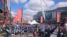 Вид на стадион Уэмбли, прилегающие здания и открытые площадки с собравшимися болельщиками