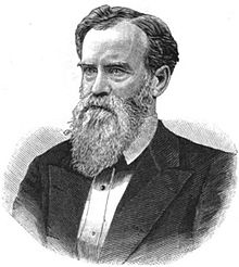 A man with black hair and a graying beard wearing a black jacket and white shirt