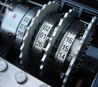 John Herivel - Three rotors inside an Enigma machine. In the middle rotor, the ring setting pin can be seen with a small red indicating arrow adjacent to the 01 position. To adjust the ring setting, the spring-loaded pin could be moved to the right to allow the ring to be turned until at the desired position.