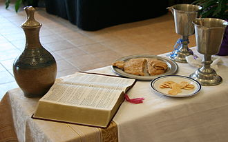 Eucharist in Lutheranism - Communion setting at an ELCA service: an open Bible, both unleavened bread and gluten-free wafers, a chalice of wine, and another with grape juice