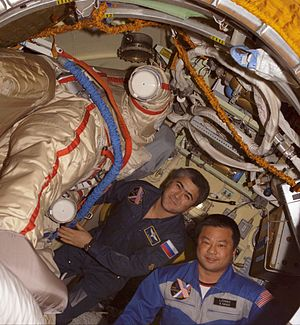 Expedition 10 - Salizhan Sharipov (left) and Leroy Chiao (right) work with their Russian Orlan spacesuits in the Pirs Docking Compartment of the International Space Station (ISS). (NASA)