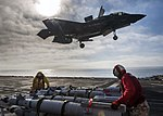 F-35B Lighting II landing on USS America (LHA-6) as sailors and marines prepare to arm it with GBU-12 Paveway II laser-guided test bombs (161105-N-VR008-0208).jpg