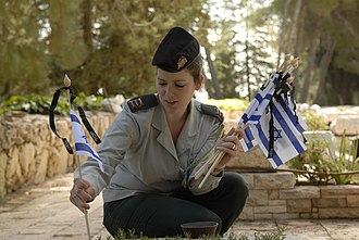 Yom Hazikaron - An IDF officer places new flags, each with a black ribbon, on the graves of IDF soldiers for Yom Hazikaron.