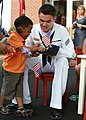 Flickr - Official U.S. Navy Imagery - A Sailor gives a Navy ball cap to a child..jpg