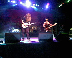 A medium sized concert stage lit in many colors. In the left stands a longhaired guitarist on the right a bass player wearing an armystyle west and helmet. In the background are two drumkits with a drummer.