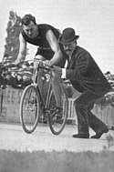 A picture of George Leander being pushed on a bike by someone.