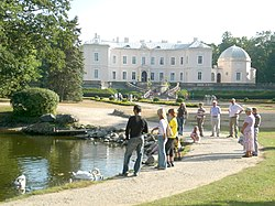 People stand around a small lake, with the back of the palace in the background.