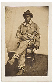 Full Length Black And White Photograph Of A Seated African American