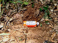 "A red palm-sized cylindrical metal container, lying in a shallow freshly dug hole in the ground, is labeled ""ENREGISTREUR DE VOL / NE PAS OUVRIR""."