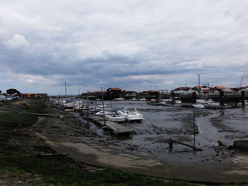 Port de Larros, port ostréicole à Gujan-Mestras (bassin d'Arcachon, Gironde, France) à marée basse. Le port de Larros comprend des activités d'ostréiculture, avec quelques cabanes d'ostréiculteurs, des activités de pêche et de chantiers navals, ainsi qu'un musée, la Maison de l'huitre sur la digue Sud du port. Voir aussi autre cliché.