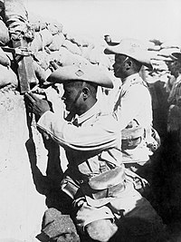 Two Gurkha soldiers in full uniform with turned-up slouch hats sit on the fire step in a fighting trench topped with sandbags. One soldier is looking through a periscope.