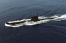 Aerial photograph of a submarine travelling on the surface of the water