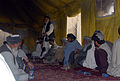 Haji Faizal Mohammad, standing, the governor of the Panjwai district of Kandahar province, Afghanistan, speaks with 30 area farmers during an agricultural shura, or meeting, at Combat Outpost Mushan in the 130328-A-ZZ999-714.jpg