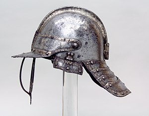 Lobster-tailed pot helmet - English helmet for a harquebusier c. 1635, with typical three-barred face protection and longitudinal comb on the skull, the laminated and hinged cheekpiece is incomplete