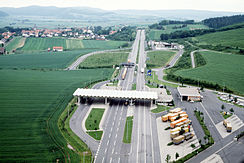 Aerial view of a four-lane motorway crossing green fields, with a small village with a church spire in the distance to the left of the motorway. In the foreground, there is a white roof structure, resting on slim white pillars, across all four lanes of the motorway; to the left, the roof also extends over a slip lane which branches off from the main road and then rejoins it; on the right, just before the roof structure, there is a parking lot with diagonally parked orange and brown lorries.