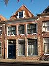 foto van Eenvoudige gevel voor wellicht ouder pand; in de vensters op de verdieping roeden. Pui modern