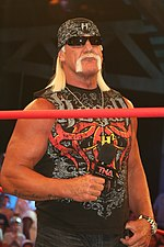Hulk Hogan standing while holding a microphone, during a TNA Impact! taping