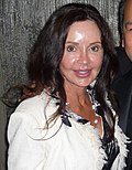 A women with brunette hair, wearing a white sweater and a black and white shirt.