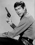 Headshot of a man holding a gun and wearing a gun belt.