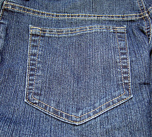 Pocket - Patch pocket with topstitching and bar tacking on the back of a pair of blue jeans.