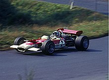 Side-view color photograph of Rindt racing a red and white Lotus Formula One car with a wing attached at the rear