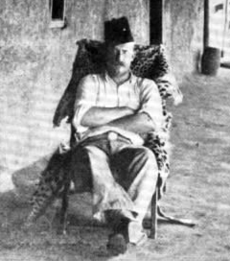 A middle-aged white man wearing a fez reclines, his arms folded, on a chair draped with a leopard skin. He wears a white shirt, the sleeves of which are rolled up to the elbows, and dark trousers.