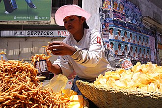 Merina people - A Merina woman selling Kakapizon (left, a fried snack) and chips in Antananarivo.