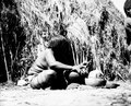 Kvinna sittande utanför hydda som tillverkar keramik. Bolivianska Chaco. Gran Chaco - SMVK - 004786.tif