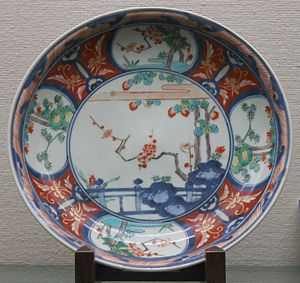 Arita ware - Arita Sarayama dish with overglaze polychrome enamel design of plum and fence, 1700-1730s, Edo period